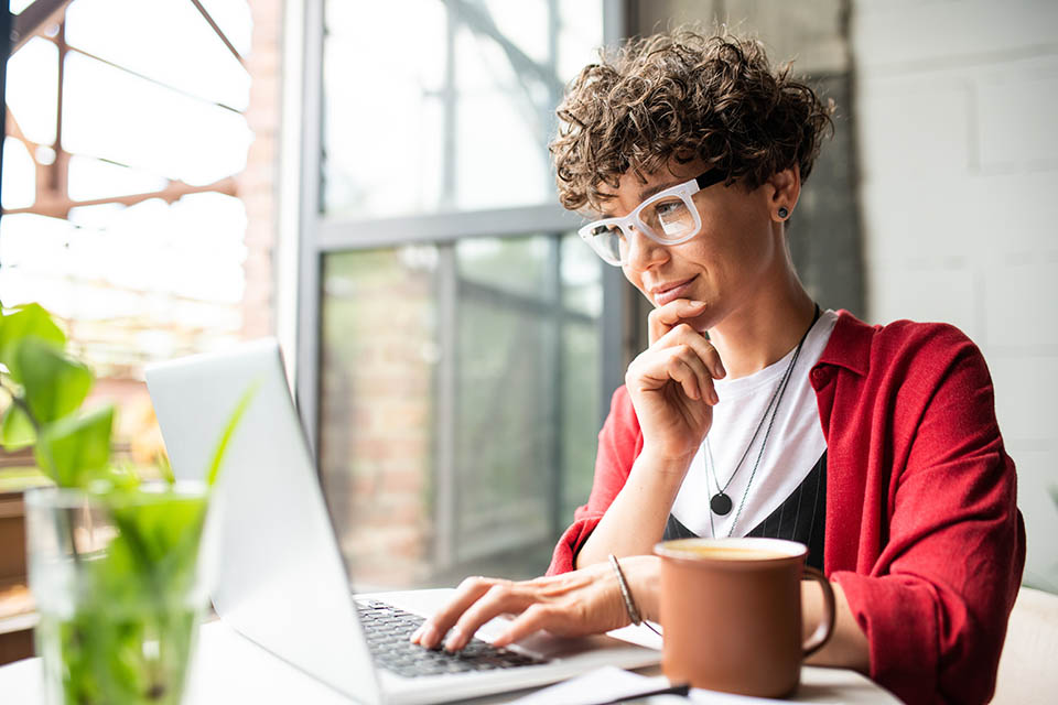 Busy young elegant woman in eyeglasses looking at laptop display while pressing keys of keypad during work